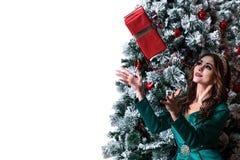 Muchacha hermosa con el pelo largo en un vestido verde con una diadema en su cabeza que coge una caja de regalo roja cerca del ár Fotografía de archivo