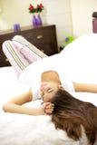 Muchacha hermosa con el pelo largo que pone en cama Foto de archivo libre de regalías