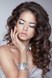 Muchacha hermosa con el pelo ondulado largo marrón maquillaje joyería Attra Imagen de archivo libre de regalías