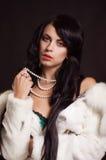 Muchacha hermosa con el pelo oscuro en un abrigo de pieles blanco Foto de archivo