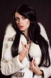 Muchacha hermosa con el pelo oscuro en un abrigo de pieles blanco Fotos de archivo libres de regalías