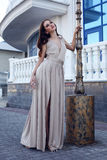 Muchacha hermosa con el pelo oscuro en vestido beige elegante Fotos de archivo