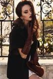 Muchacha hermosa con el pelo oscuro que lleva la capa elegante y los guantes de cuero imagenes de archivo