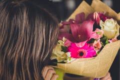Muchacha hermosa con el pelo oscuro con un ramo de flores de un lirio, de un gerbera, de rosas blancas y de un alstroemeria en un Fotos de archivo libres de regalías