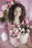 Muchacha hermosa con el pelo rizado, adolescente con los tulipanes de las flores a disposición Imagenes de archivo