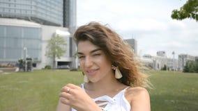 Muchacha hermosa con el pelo rizado oscuro mirada en la cámara en un parque de la ciudad metrajes
