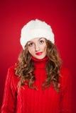 Muchacha hermosa con el pelo rizado que lleva el sombrero caliente y el suéter rojo Foto de archivo