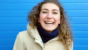 Muchacha hermosa con el pelo rizado que sonríe, riendo contra la pared azul almacen de metraje de vídeo