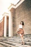 Muchacha hermosa con el pelo rizado y la falda largos outdoor Foto de archivo