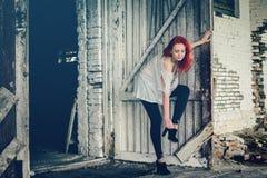 Muchacha hermosa con el pelo rojo al aire libre contra puertas de madera Imágenes de archivo libres de regalías