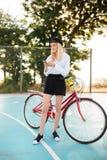 Muchacha hermosa con el pelo rubio en camisa y pantalones cortos que se colocan con la bicicleta roja en la cancha de básquet en  Fotografía de archivo libre de regalías