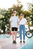 Muchacha hermosa con el pelo rubio en gafas de sol y la situación fresca del muchacho y soñador la mirada in camera con dos bicic Fotografía de archivo