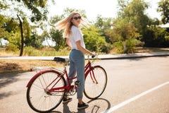 Muchacha hermosa con el pelo rubio en las gafas de sol que se colocan con la bicicleta clásica roja que mira soñador in camera Ch Fotos de archivo