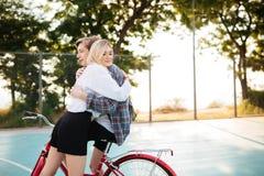 Muchacha hermosa con el pelo rubio que mira soñador a un lado mientras que abraza al muchacho pensativo en la bicicleta roja clás Imagenes de archivo