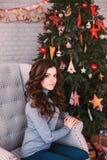 Muchacha hermosa con el pelo y maquillaje cerca del árbol de navidad Foto de archivo libre de regalías