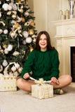 Muchacha hermosa con el regalo a disposición, sentándose en la alfombra cerca del árbol de navidad Foto de archivo libre de regalías