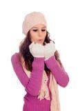 Muchacha hermosa con el sombrero y la bufanda de las lanas que soplan sus manos Fotografía de archivo