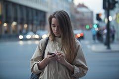 Muchacha hermosa con el teléfono en la ciudad de la tarde Imágenes de archivo libres de regalías
