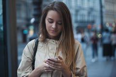 Muchacha hermosa con el teléfono en la ciudad de la tarde Imagen de archivo libre de regalías