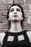Muchacha hermosa con el vestido negro y los pendientes que miran para arriba, pared hecha de ladrillos Imagen de archivo