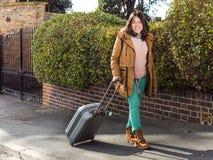 Muchacha hermosa con equipaje que camina a través de la calle Fotos de archivo