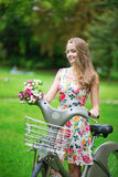Muchacha hermosa con la bicicleta en el campo Imágenes de archivo libres de regalías