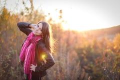 Muchacha hermosa con la bufanda rosada en la puesta del sol en un campo Retrato en la puesta del sol, luz ámbar, fondo hermoso Fotografía de archivo libre de regalías