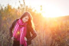 Muchacha hermosa con la bufanda rosada en la puesta del sol en un campo Retrato en la puesta del sol, luz ámbar, fondo hermoso Imagen de archivo