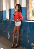 Muchacha hermosa con la camisa roja y los pantalones cortos blancos que presentan en pasillo viejo con el azul de las columnas pi Imagen de archivo libre de regalías