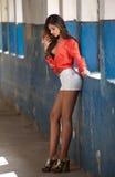 Muchacha hermosa con la camisa roja y los pantalones cortos blancos que presentan en pasillo viejo con el azul de las columnas pi Foto de archivo libre de regalías