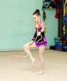 Muchacha hermosa con la cuerda de salto en el entrenamiento de la gimnasia del arte Imagen de archivo libre de regalías