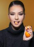 Muchacha hermosa con la estación de la vitamina C de la mandarina de la fruta cítrica y el concepto sano Imágenes de archivo libres de regalías