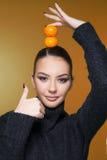 Muchacha hermosa con la estación de la vitamina C de la mandarina de la fruta cítrica y el concepto sano Imagenes de archivo