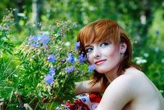 Muchacha hermosa con la flor azul foto de archivo