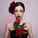 Muchacha hermosa con la flor de las rosas rojas Imágenes de archivo libres de regalías