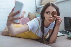 muchacha hermosa con la galleta que toma el selfie en smartphone mientras que miente en el sofá fotos de archivo