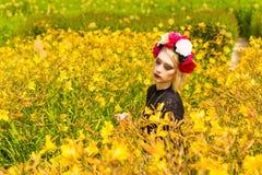Muchacha hermosa con la guirnalda de flores salvajes en su cabeza Imágenes de archivo libres de regalías