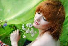 Muchacha hermosa con la hierba de la milenrama fotografía de archivo
