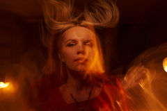 Muchacha hermosa con la llama en fondo negro Imágenes de archivo libres de regalías