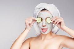 Muchacha hermosa con la máscara aplicada de la arcilla en el fondo gris Foto de archivo libre de regalías