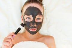 Muchacha hermosa con la máscara negra facial de la arcilla Fotos de archivo