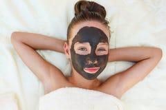 Muchacha hermosa con la máscara negra facial de la arcilla Fotografía de archivo libre de regalías