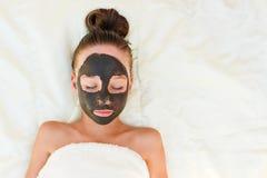 Muchacha hermosa con la máscara negra facial de la arcilla Imagenes de archivo