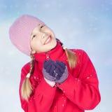 Muchacha hermosa con la nieve en manos, fondo azul Imagen de archivo