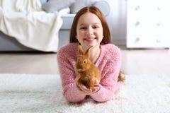 Muchacha hermosa con la pequeña mentira del conejo Foto de archivo