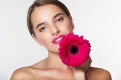 Muchacha hermosa con la piel perfecta que sostiene la flor del gerbera Imagen de archivo