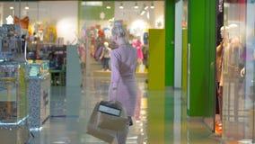 Muchacha hermosa con la presentación de los panieres, ligando en centro comercial