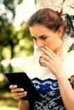 Muchacha hermosa con la tableta digital en parque Imagenes de archivo