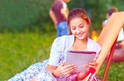 Muchacha hermosa con la tableta en comida campestre del verano Imágenes de archivo libres de regalías