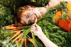 Muchacha hermosa con la zanahoria sabrosa imagen de archivo libre de regalías